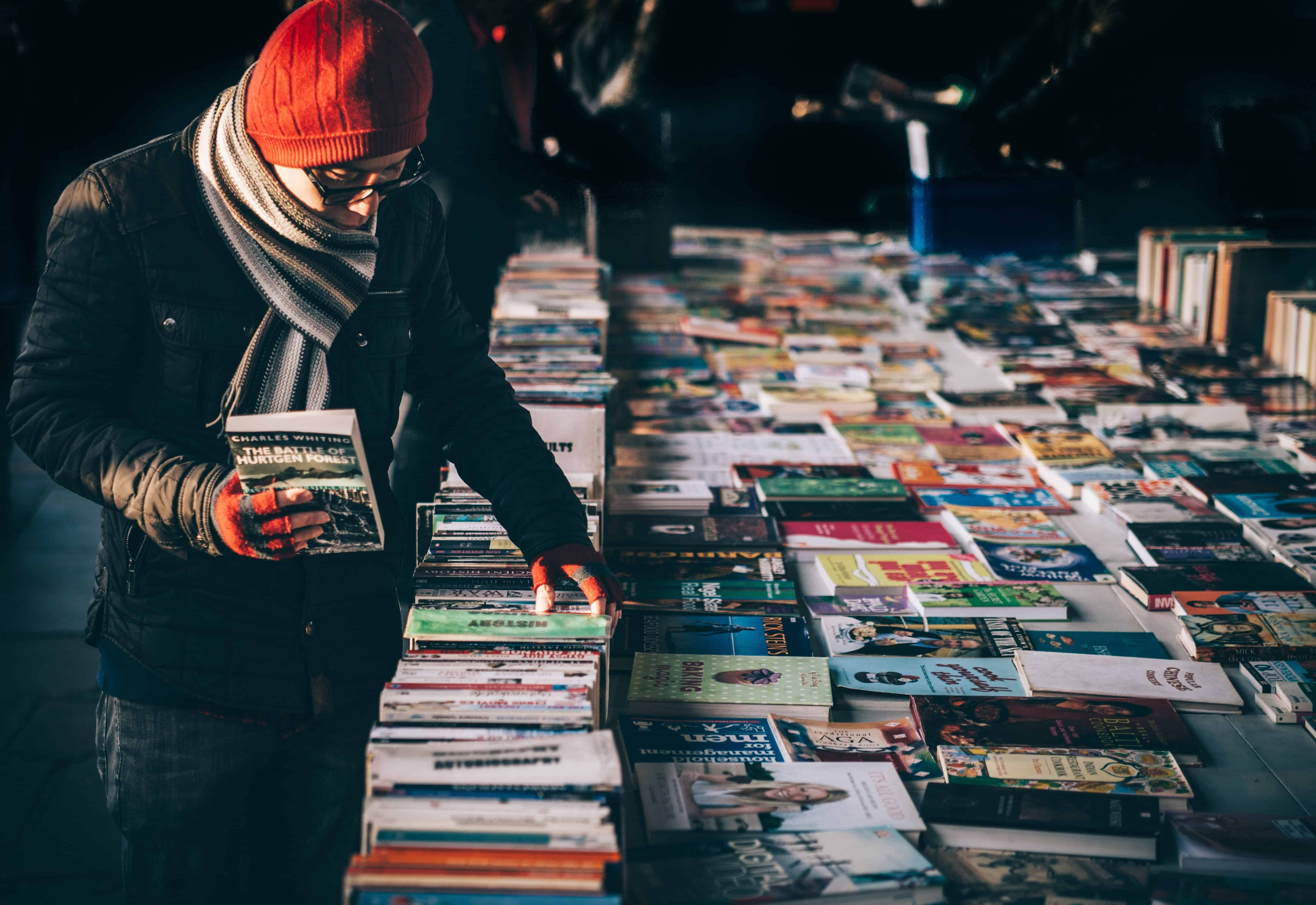 Man dressed in winter clothes looking at a book stall on the street with one book in his hand.